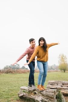 Jeune couple, équilibre, sur, tronc arbre
