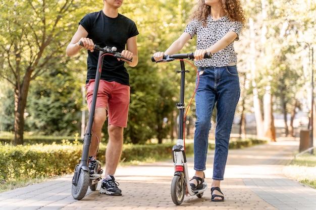 Jeune couple, équitation, scooters, dehors