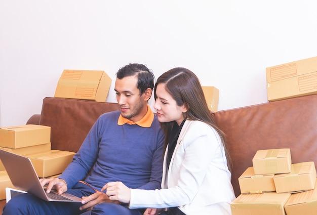Jeune couple est ajouté aux achats en ligne, plein de boîtes livrées
