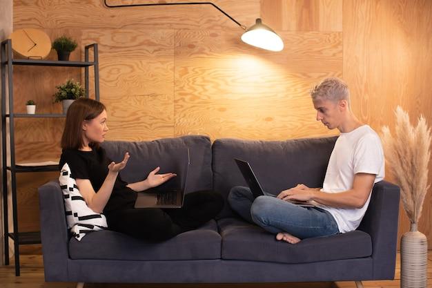 Jeune couple est assis sur le canapé et jure. la fille est très malheureuse