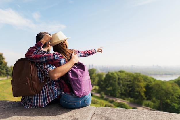 Un jeune couple est assis sur un parapet.