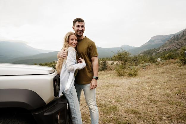 Le jeune couple est en voyage romantique à la montagne en voiture