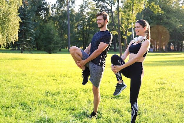 Jeune couple étirant leurs jambes ensemble tout en travaillant au parc à l'extérieur.