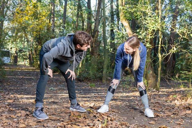Jeune couple étirement des muscles avant le jogging dans la nature