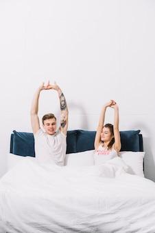 Jeune couple, étirer bras, dans lit