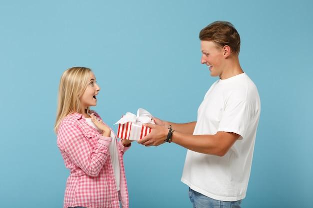 Jeune couple étonné deux amis mec et femme en t-shirts roses blancs posant