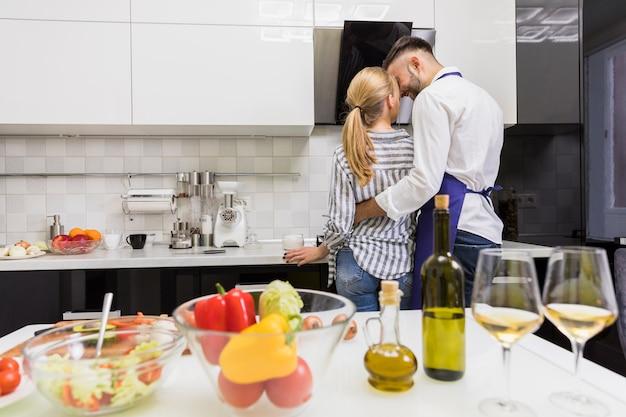 Jeune couple, étreindre, dans cuisine