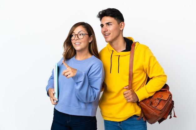 Jeune couple étudiant sur blanc présentant une idée tout en regardant en souriant vers