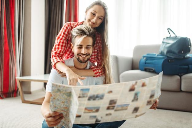 Jeune couple étudiant une carte avant le voyage d'été