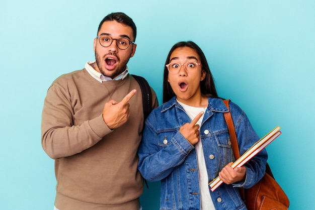 Jeune couple étudiant métisse isolé sur fond bleu pointant vers le côté