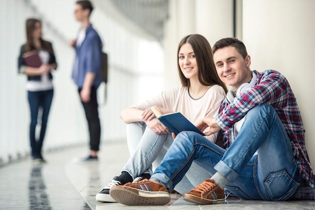 Jeune couple d'étudiants assis dans le couloir au collège.
