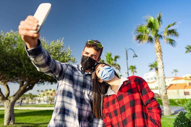 Un jeune couple d'étudiants en chemise à carreaux prend un selfie avec un masque de protection en raison de la pandémie de coronavirus.