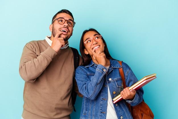 Jeune couple d'étudiants métis isolé sur bleu détendu en pensant à quelque chose en regardant un espace de copie.