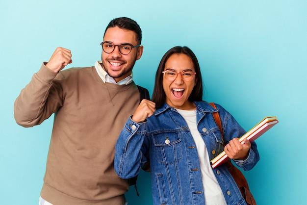 Jeune couple d'étudiants métis isolé sur fond bleu levant le poing après une victoire, concept gagnant.