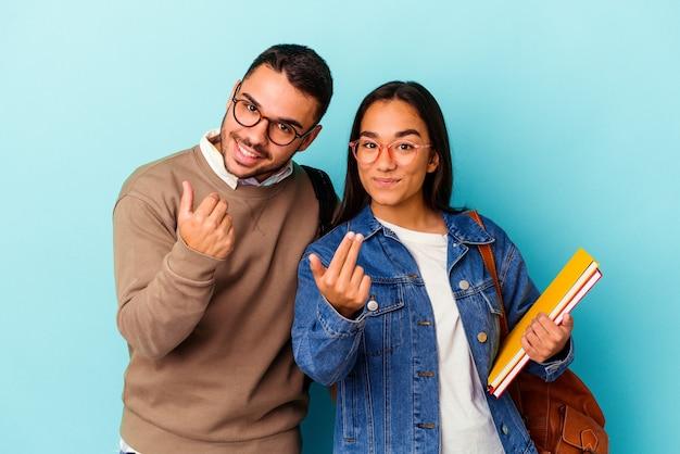 Jeune couple d'étudiants métis isolé sur fond bleu pointant du doigt vers vous comme si vous invitiez à vous rapprocher.