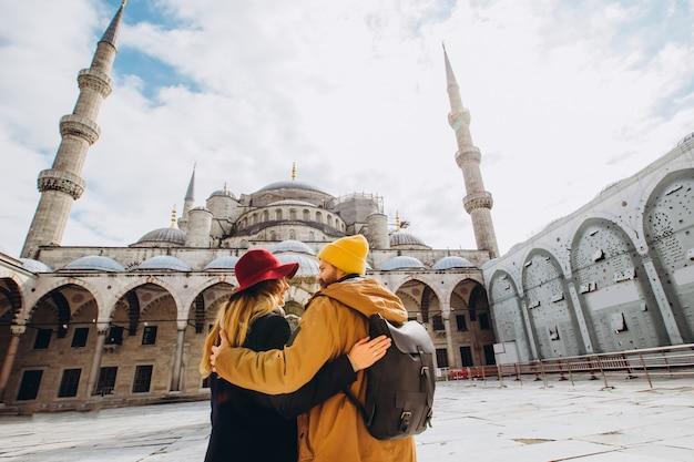 Un jeune couple européen se promène dans la cour de la mosquée bleue à istanbul, turquie. voyageur gars et fille en chapeaux jaunes à pied en hiver istanbul. jour d'automne nuageux à istanbul.
