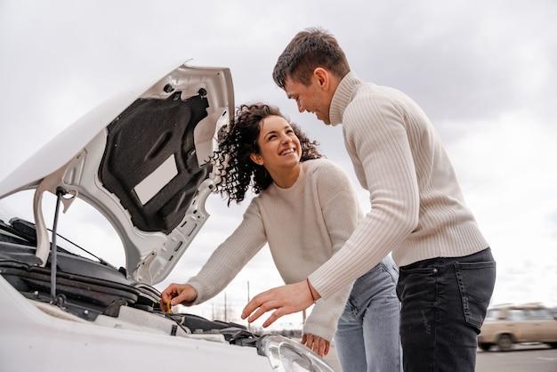 Jeune couple européen vérifier le capot de la voiture à l'extérieur. faible angle de vue de l'homme et de la femme bouclée se regardant. personnes heureuses et souriantes. concept de profiter du temps ensemble
