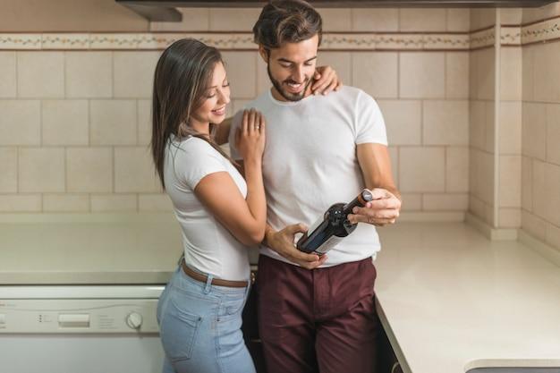 Jeune couple, examiner, bouteille vin