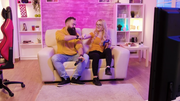 Jeune couple excité assis sur un canapé et jouant à des jeux vidéo à l'aide de contrôleurs sans fil. chaise de jeu. lumière colorée.
