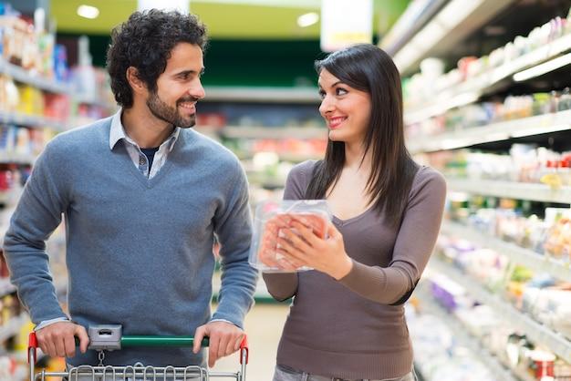 Jeune couple, faire du shopping dans un supermarché