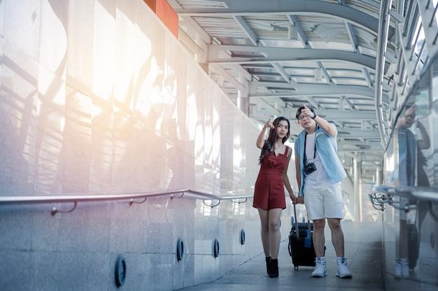 Jeune couple avec faire glisser une valise et parler tout en voyageant dans la ville.