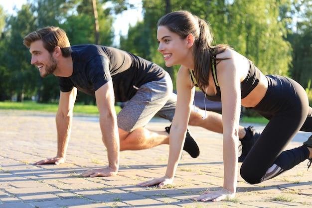Jeune couple faisant de l'exercice ensemble tout en travaillant à l'extérieur dans le parc.
