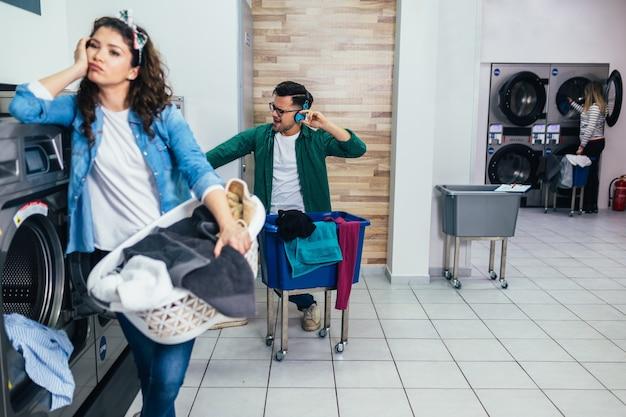 Jeune couple faisant la lessive ensemble à la laverie.