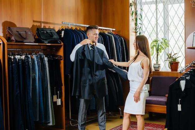 Un jeune couple fait du shopping et prend un costume d'homme.