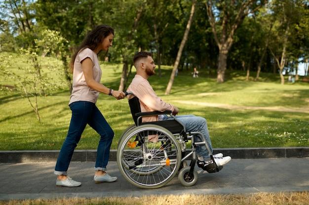 Jeune couple familial en fauteuil roulant marchant dans le parc. personnes paralysées et handicaps, prise en charge d'un homme handicapé. mari et femme surmontent les difficultés ensemble, relations chaleureuses