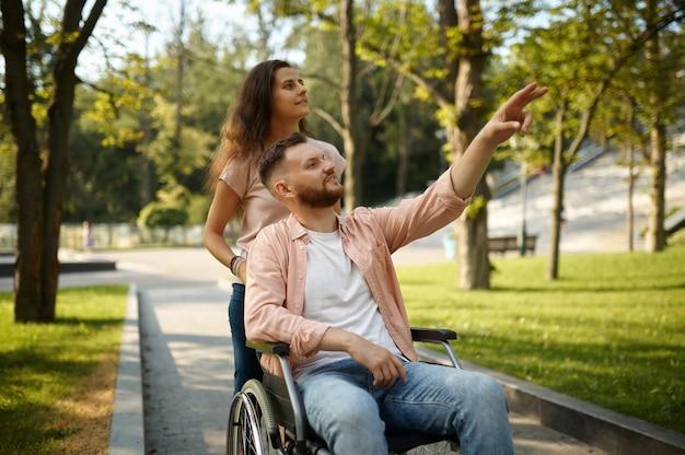 Jeune couple familial en fauteuil roulant marchant dans le parc. personnes paralysées et handicaps, prise en charge d'un homme handicapé. le mari et la femme surmontent les difficultés ensemble