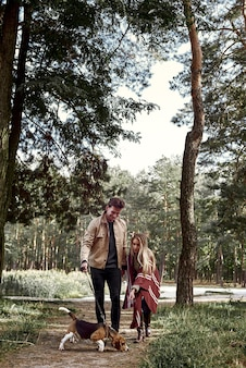 Un jeune couple familial marche dans les bois avec son chien. une femme élégante essaie de nourrir le chien. le soleil brillant brille, jette les arbres, hors saison