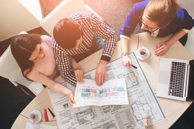 Jeune couple de famille achète un bien immobilier à louer. agent donnant une consultation à l'homme et à la femme