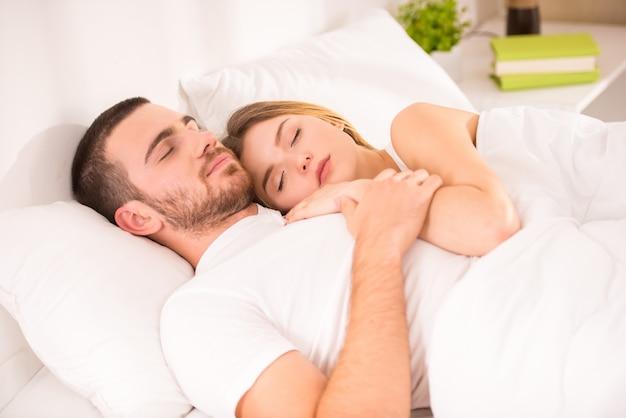 Jeune couple fatigué au lit à la maison ensemble.