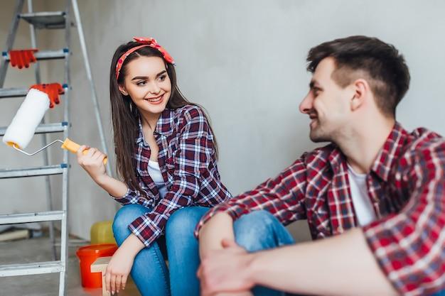 Un jeune couple fatigué est assis sur le sol avec un pinceau et un seau tout en faisant des réparations à la maison