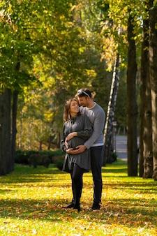 Jeune couple avec femme enceinte debout dans un parc à l'automne dans une étreinte étroite berçant son estomac alors qu'ils se lient avec leur enfant à naître