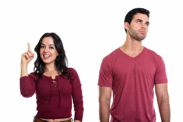 Jeune couple avec une femme heureuse souriant et pointant vers le haut