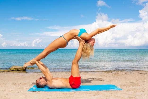 Jeune couple femme et hommes sur la plage, faire des exercices de yoga fitness ensemble. élément acroyoga pour la force et l'équilibre