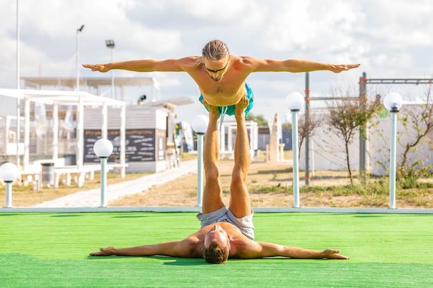 Jeune couple femme et hommes sur le terrain, faire des exercices de yoga fitness ensemble. élément acroyoga pour la force et l'équilibre