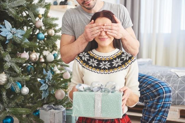 Jeune couple fête noël. un homme a soudainement présenté un cadeau à sa femme. le concept de bonheur et de bien-être familial