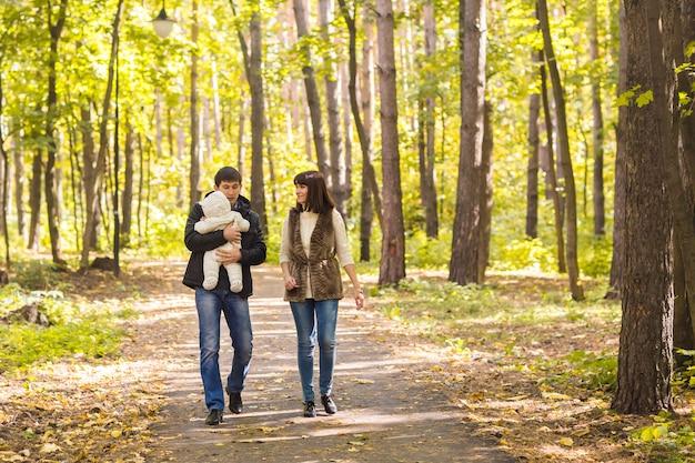 Jeune couple avec fils nouveau-né à l'extérieur à l'automne