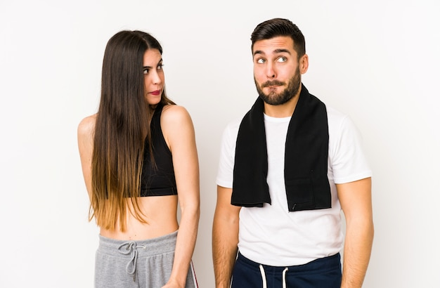 Jeune couple de fitness caucasien confus, se sent douteux et incertain.