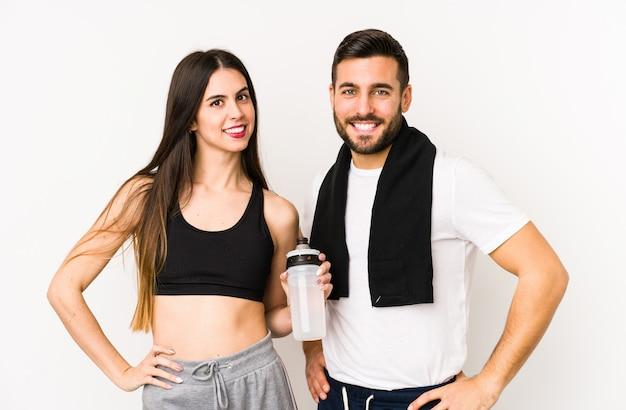 Jeune couple de fitness caucasien isolé confiant en gardant les mains sur les hanches.