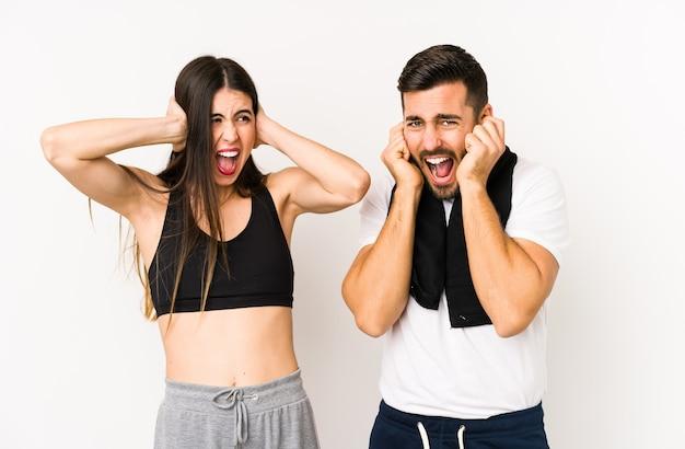 Jeune couple de fitness caucasien isolé couvrant les oreilles avec les mains en essayant de ne pas entendre un son trop fort.