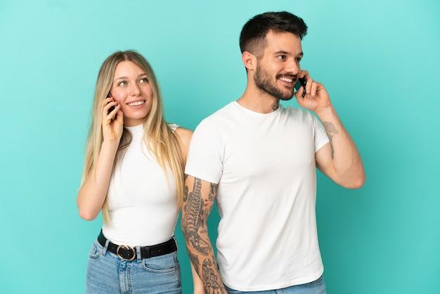 Jeune couple sur fond bleu isolé parlant au mobile