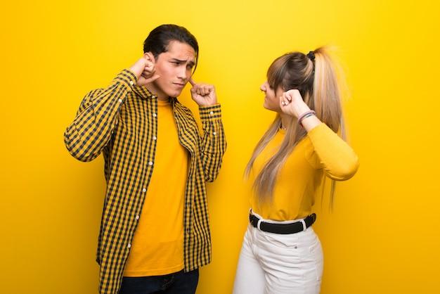 Jeune couple sur fond jaune vibrant couvrant les deux oreilles avec les mains