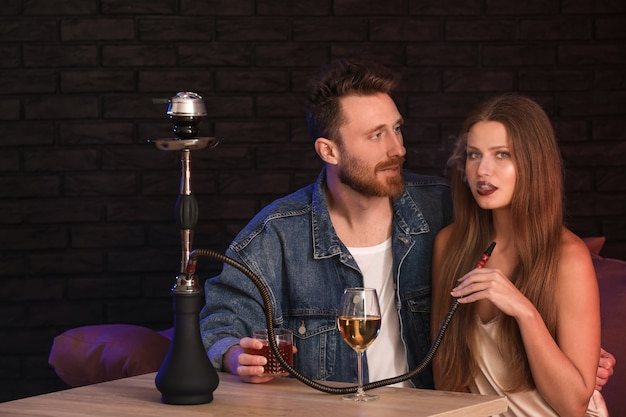 Jeune couple, fumer, narguilé, dans, café