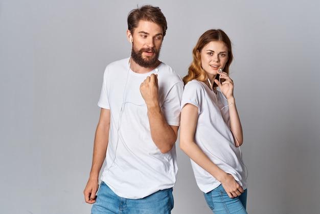 Jeune couple gai dans des écouteurs écoutant le fond clair de divertissement de musique