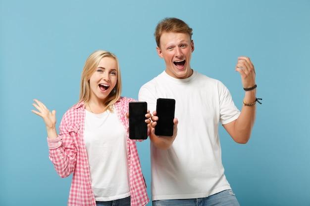 Jeune couple gai deux amis homme et femme en t-shirts roses blancs posant
