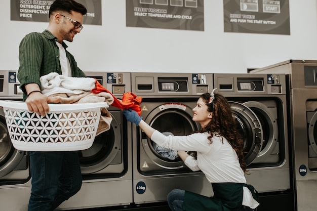 Jeune couple gai faisant la lessive ensemble à la laverie automatique.