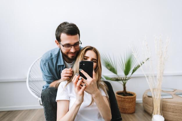 Jeune couple gai utilisant un téléphone mobile, faisant selfie sur smartphone ensemble
